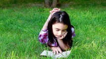 Little girl reading a book in summer park on grass