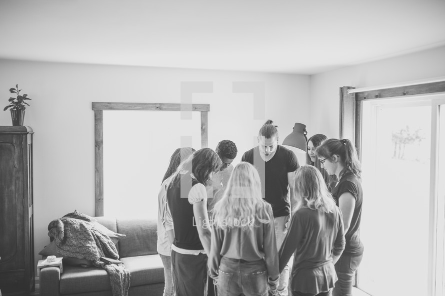 group holding hands in a prayer circle
