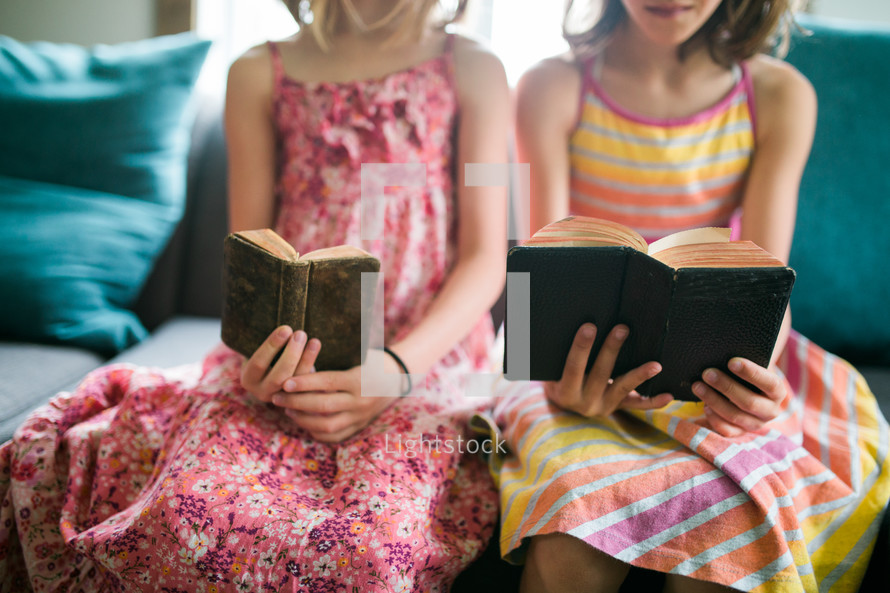 two girls reading from old Bibles