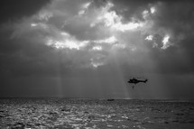Helicopter flying over the ocean