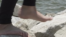 walking barefoot on rocks along a shore