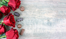 chocolates and red roses on a wood background