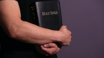 a man holding a Bible close to his chest