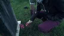 a girl putting flowers on a grave
