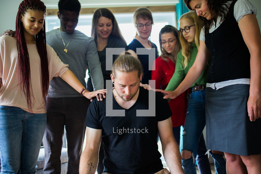 group laying hands on a man praying over him