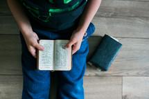 a boy reading a Bible