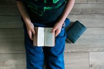a boy reading a pocket Bible