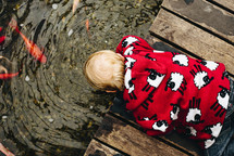 a toddler looking into a koi pond