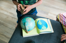 children reading a Bible and playing with a globe