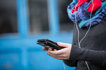 a woman listening to earbuds and holding a tablet