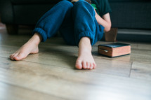 a boy sitting on the floor reading a Bible