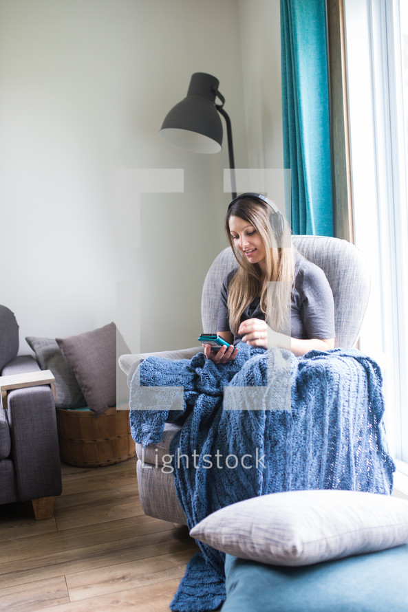 a woman sitting in a chair listening to a Bible app with headphones