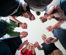 group holding hands in a pray circle