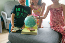 kids playing with a globe and reading a Bible