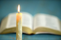 melting candle in front of an open Bible