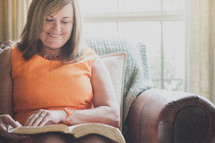 Joyful woman reading her Bible.