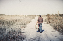 man walking down a dirt road with a suitcase