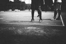 Men's legs on a basketball court.