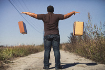 man throwing down luggage on a dirt road