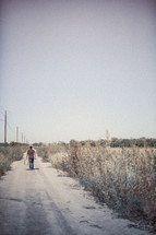 man walking down a dirt road with luggage