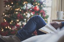 man reading a Bible on a couch in front of a Christmas tree