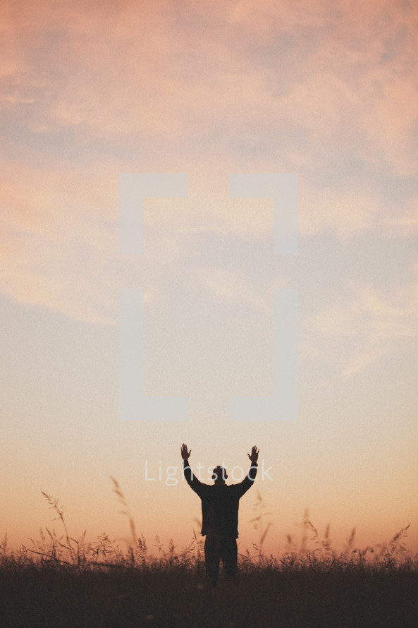 silhouette of a man with his hands raised to God