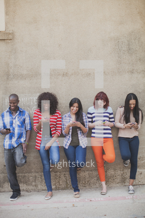 a row of young adults texting on their cellphones