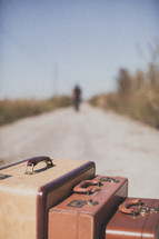luggage and a man walking down a dirt road