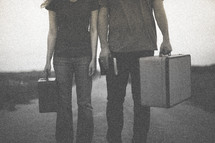 man and woman carrying suitcases and holding a Bible