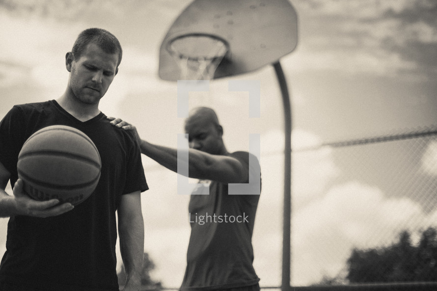 Men praying on a basketball court while holding a basketball.
