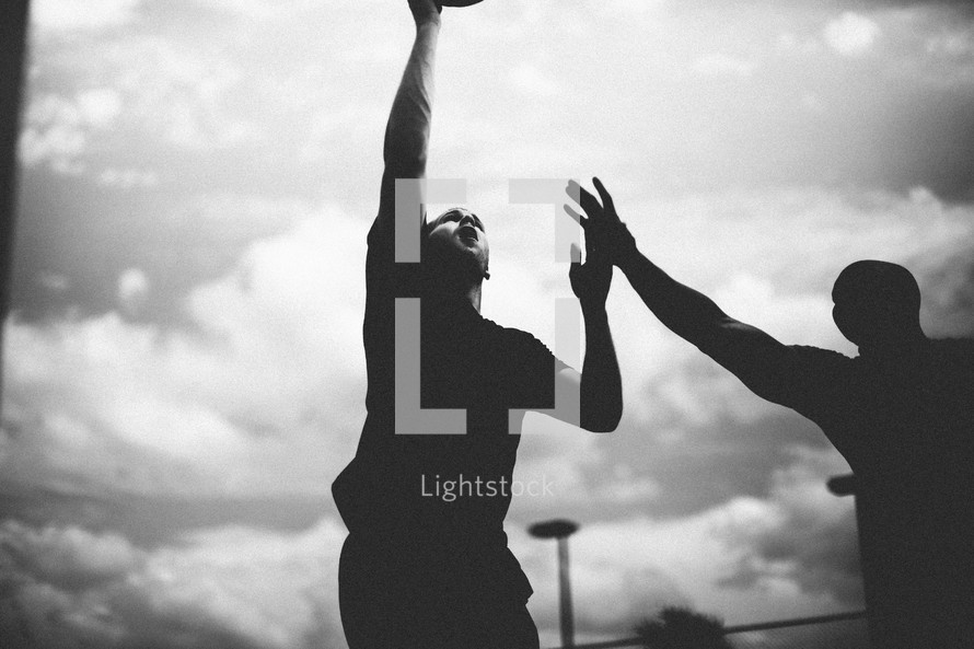 Silhouette of men playing basketball.