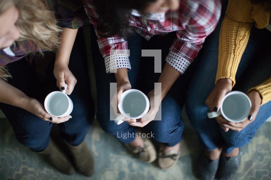 woman holding empty coffee mugs