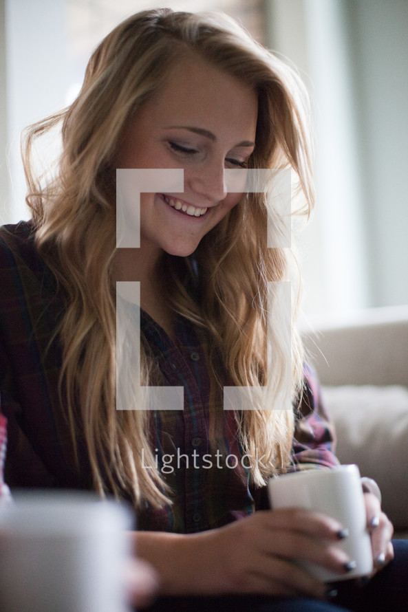 a young woman holding a coffee mug