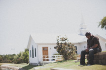 man in prayer outside of a church
