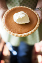 woman holding a pumpkin pie