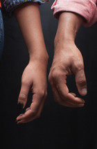 man and woman standing next to each other touching hands