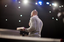 a man preaching at a pulpit with the Bible in his hands