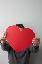 man holding a large red paper heart