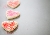 red and pink sprinkles on heart shaped cookies