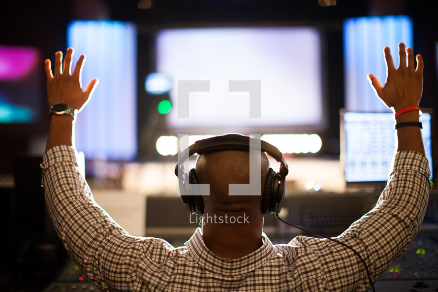 a man working a sound board with hands raised and a head set on