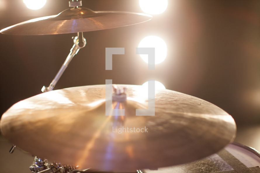 Stage lights shining on cymbals.