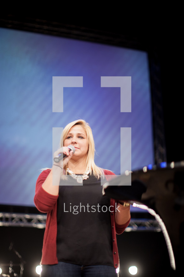 a woman with a microphone at the pulpit
