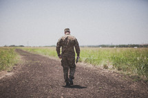 serviceman walking down a dirt road