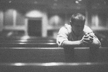 man alone in prayer in an empty church