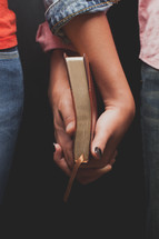 couple hands clasped holding a Bible