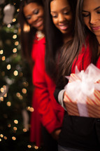 three African-American women with heads bowed holding a wrapped Christmas gift