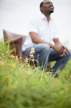 man sitting in a chair outdoors praying