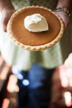 woman holding a pumpkin pie