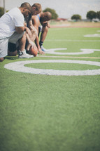 men in prayer on a football field
