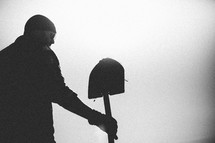 A man stands under a gray sky holding a shovel.